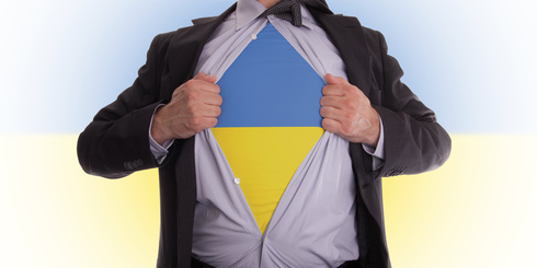 Business man rips open his shirt to show his Ukrainian flag t-shirt